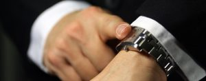 A businessman looking at his watch, deadline/due theme